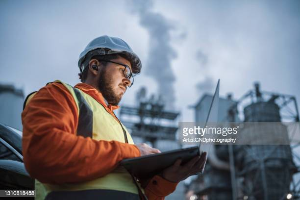 serious handsome engineer using a laptop while working in the oil and gas industry. - equipment stock pictures, royalty-free photos & images