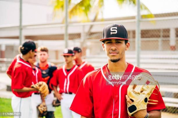 グローブを持つ深刻なヒスパニックの野球選手がプレーするのを待っている - 高校野球 ストックフォトと画像