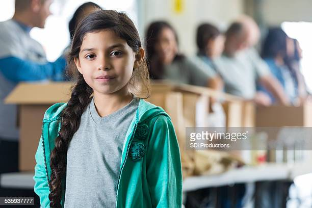 Serious Hispanic child in front of volunteers sorting food donations
