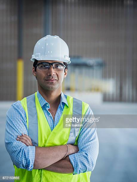 Serious Indian worker in empty warehouse