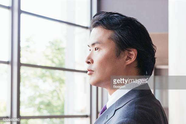 Serious Japanese Businessman Looking Out Window in Contemplation