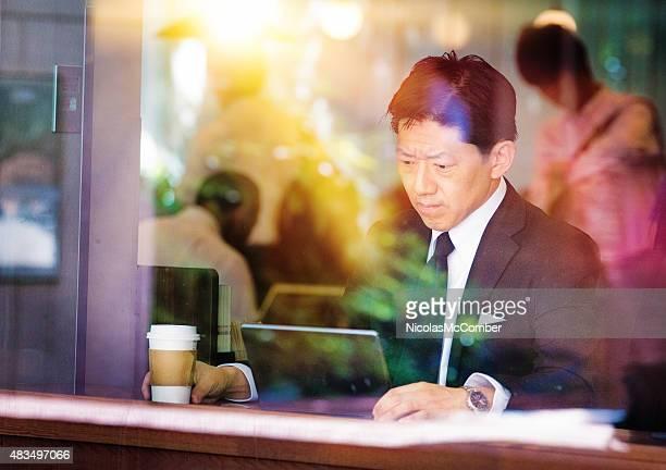 本格的な日本の実業家のタブレットを見に不幸せなカフェ