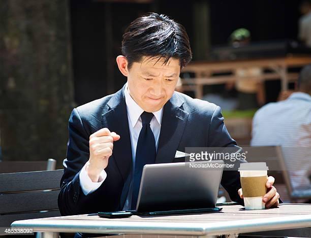 本格的な日本の実業家のタブレットを眺めながら、屋外でのスポーツイベント