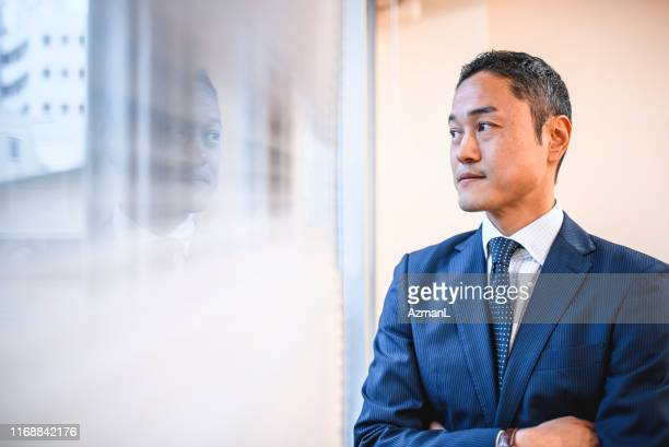 serious japanese hospital administrator looking out window - solo un uomo di età media foto e immagini stock