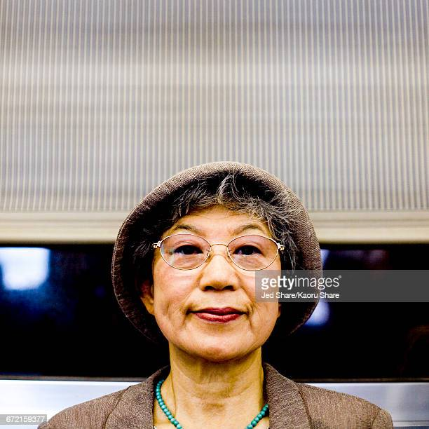 Serious Japanese woman wearing hat and eyeglasses