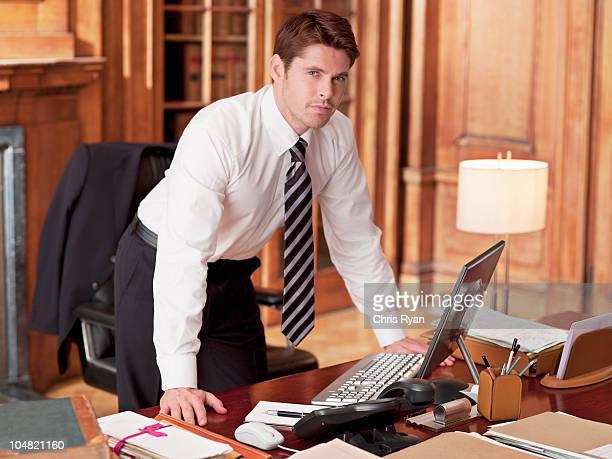 Abogado serio trabajando en el ordenador portátil en oficina