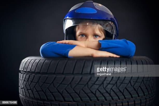 Serious little boy looking at camera from stack of tyres