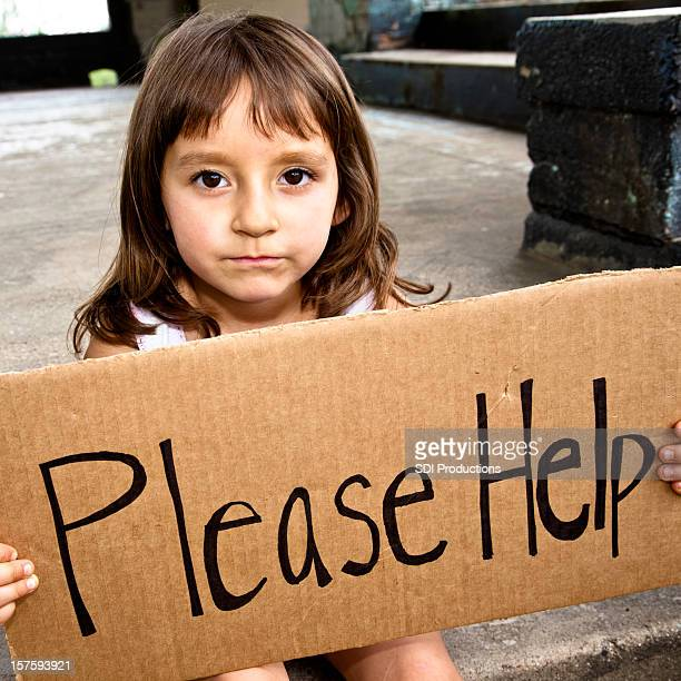 serious little girl holding a please help sign - s and m stock photos and pictures