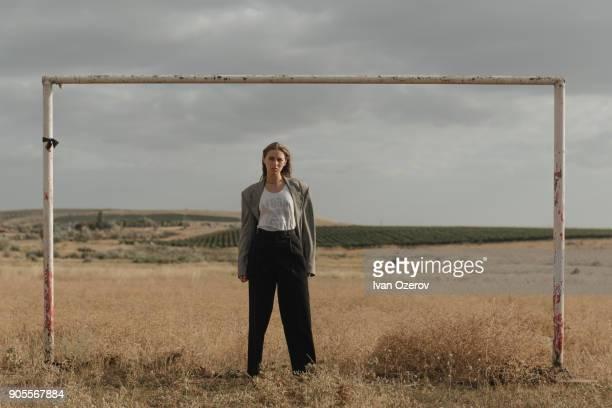 serious location woman standing in worn soccer goal - junge frau allein stock-fotos und bilder