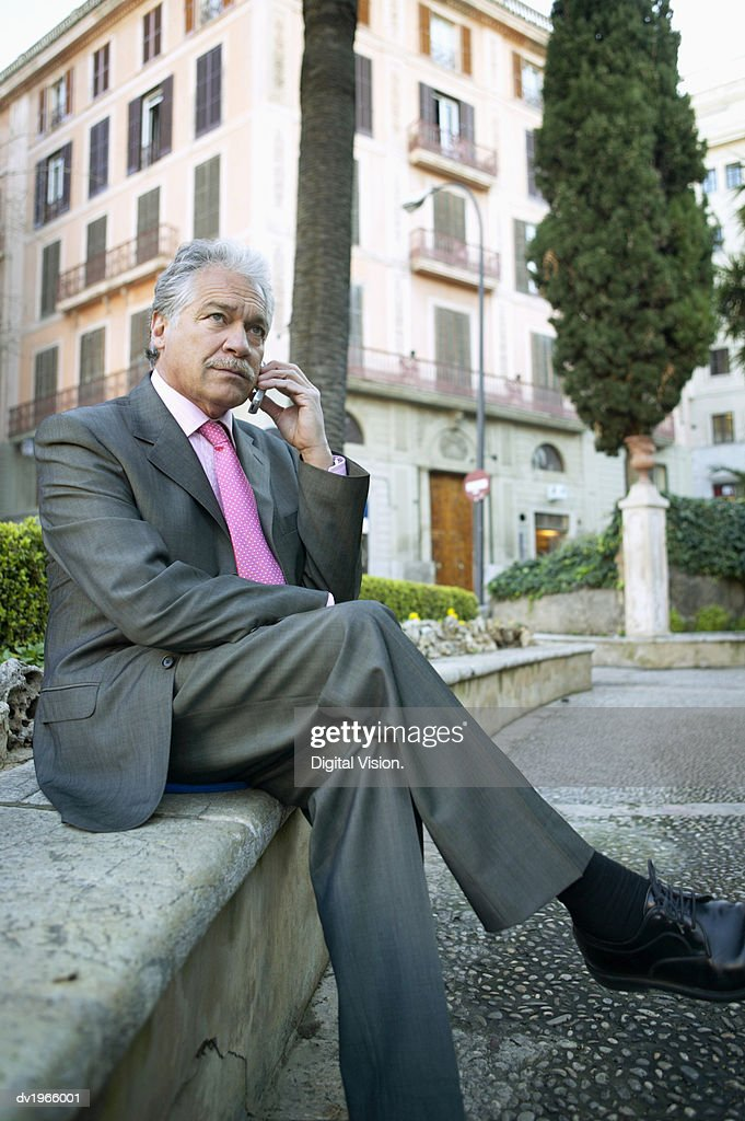 Serious Looking Businessman Sits Outside Using His Mobile Phone : Stock Photo