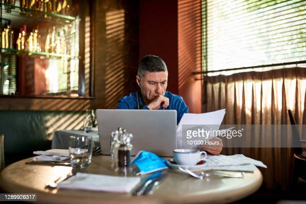 serious looking man reading document in restaurant with face mask on table - finance and economy stock pictures, royalty-free photos & images