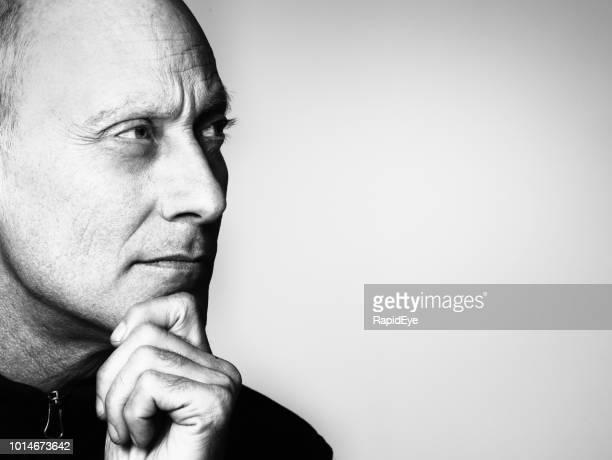 sérieux cherche homme mûr, main sur menton, regarde sur le côté - image en noir et blanc photos et images de collection