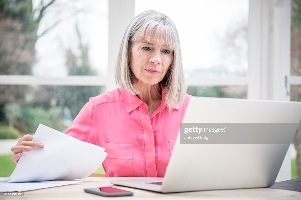 Serious looking senior woman with laptop and paperwork : Stock Photo