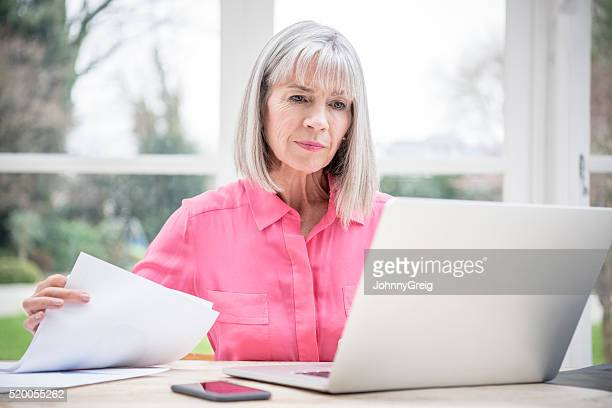 serious looking senior woman with laptop and paperwork - adults only stock pictures, royalty-free photos & images
