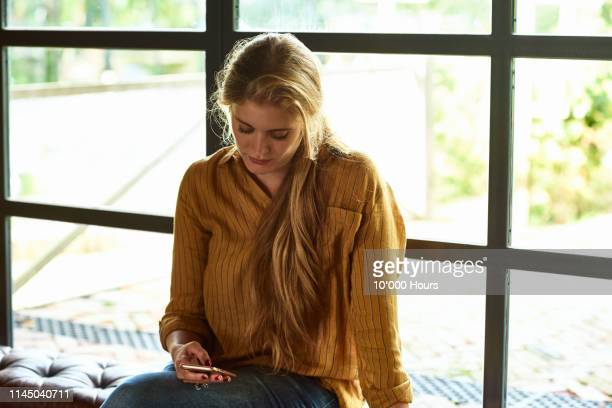serious looking woman by window reading phone message - candid forum stock pictures, royalty-free photos & images