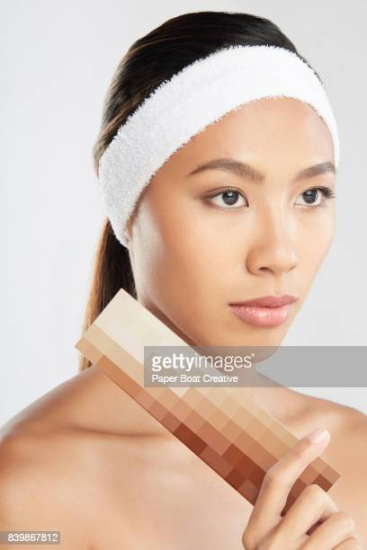Serious looking woman holding a brown skin catalog and putting it near hear skin to see which is her correct shade