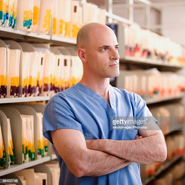 Serious male doctor with arms crossed in medical records room