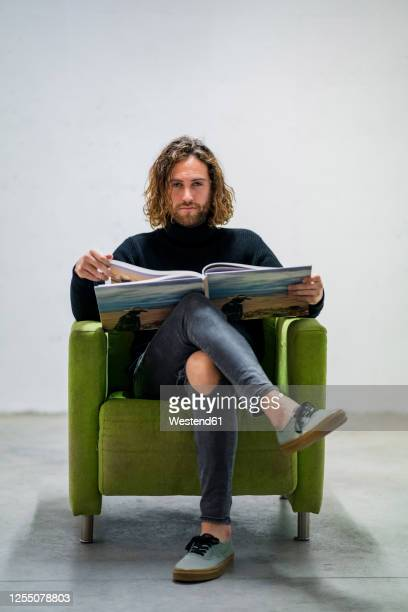 serious man holding book while sitting on armchair against wall at home - armchair stock pictures, royalty-free photos & images