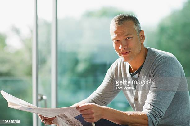 Serious man holding newspaper