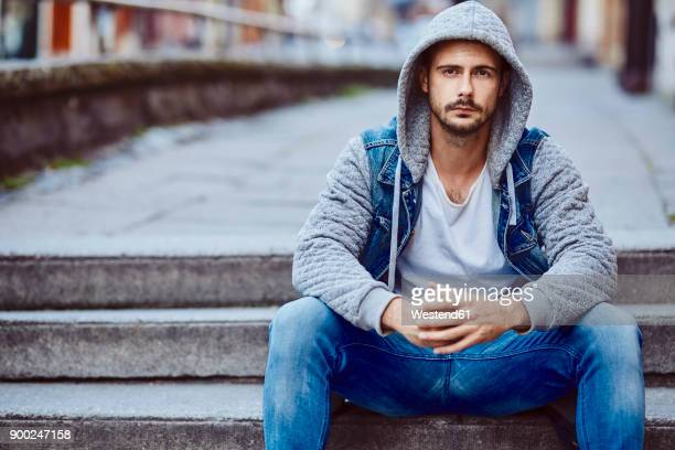 serious man in hooded jacket sitting on stairs - hood clothing stock photos and pictures