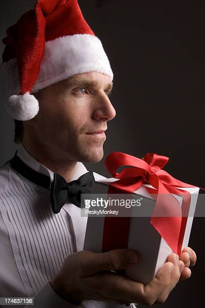 Serious Man in Santa Hat Holds Christmas Holiday Gift