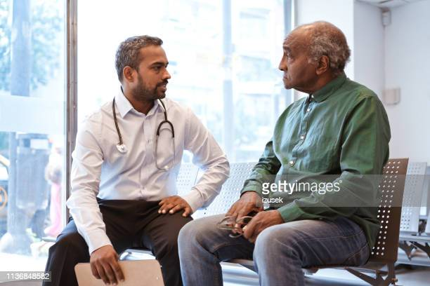serious man is staring at doctor in waiting room - outpatient care stock pictures, royalty-free photos & images