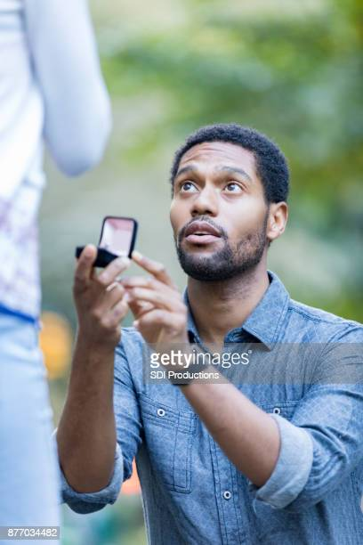 serious man kneels while proposing to girlfriend - engagement ring box stock photos and pictures