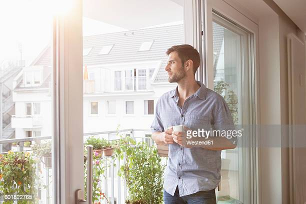 Serious man looking out of window