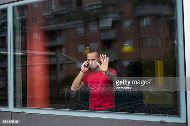 Serious man on the phone looking through window