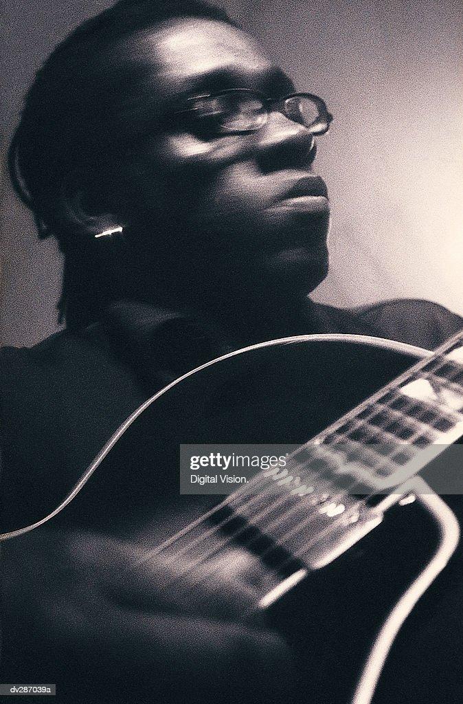 Serious man playing guitar : Stock Photo