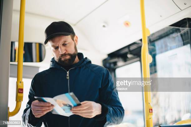 Serious man reading map while standing in bus on sunny day