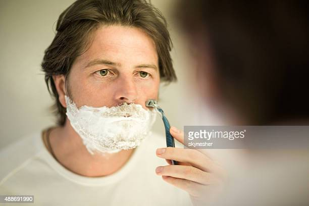 serious man shaving with razor in bathroom. - razor stock photos and pictures