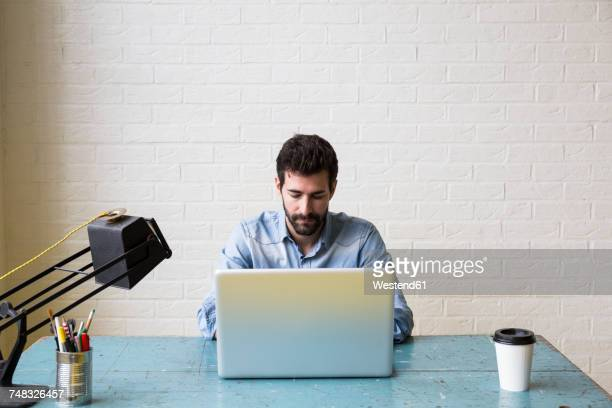 Serious man sitting at desk working with his laptop