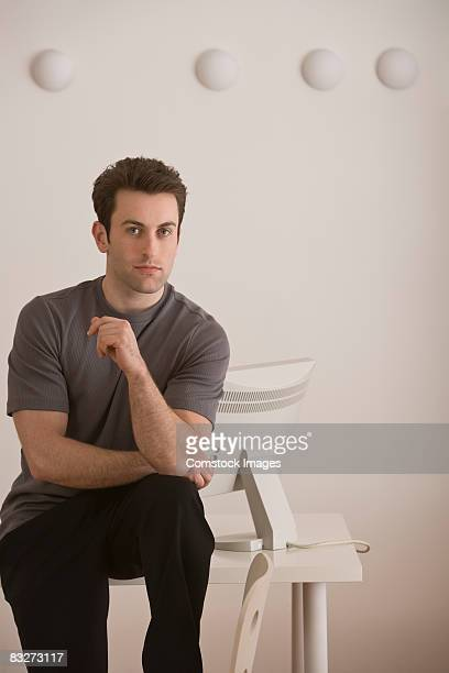 Serious man sitting on desk