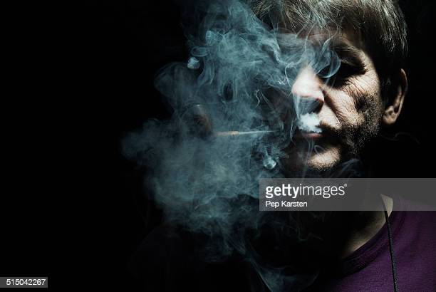 A serious man smoking a pipe, staring ominously into the camera