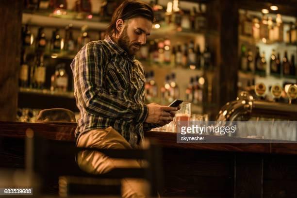 Ernstige man van het tekstoverseinen op slimme telefoon terwijl het besteden van zijn tijd in een pub.
