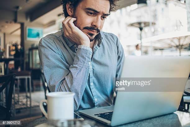 深刻な男性ノートパソコンを使う