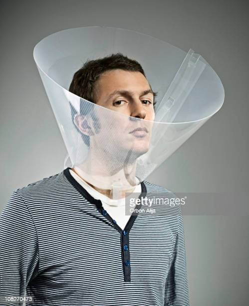 serious man wearing dog cone - elizabethan collar stock photos and pictures