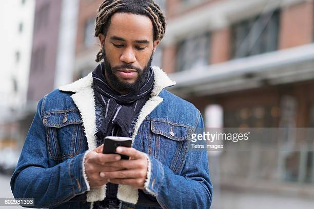 Serious man with dreadlocks using smart phone in street