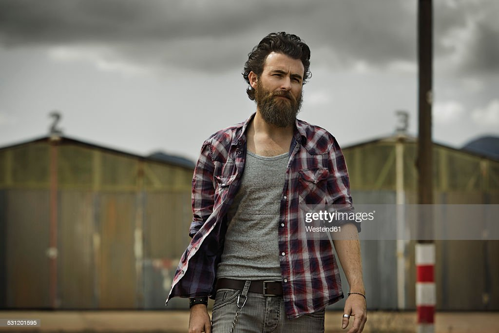 Serious man with full beard in abandoned landscape : Stock Photo