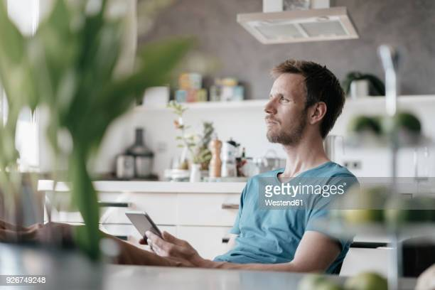 serious man with tablet sitting in the kitchen with feet up looking at distance - looking at view stock-fotos und bilder