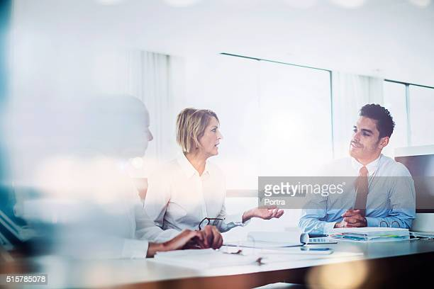 Serious manager discussing with executives at desk