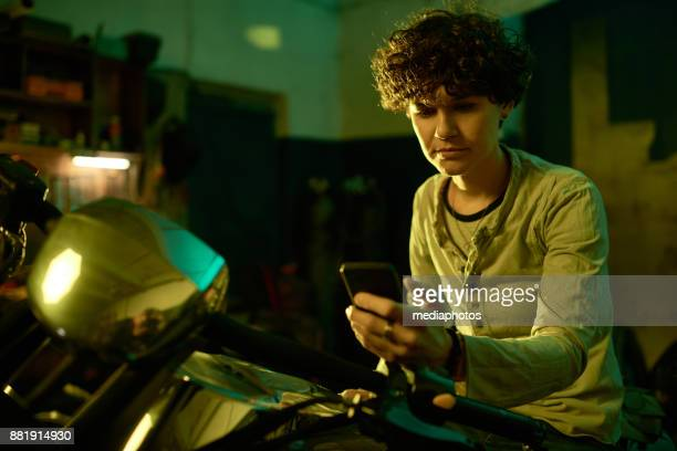 Serious masculine woman checking sms in garage