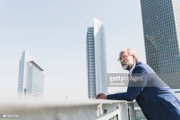 serious mature businessman in the city looking around - sehen stock-fotos und bilder
