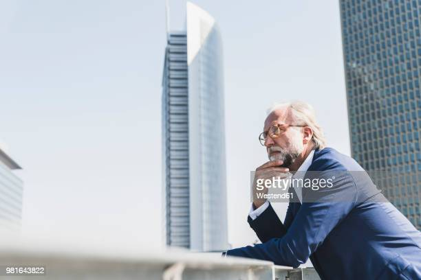 Serious mature businessman in the city looking around