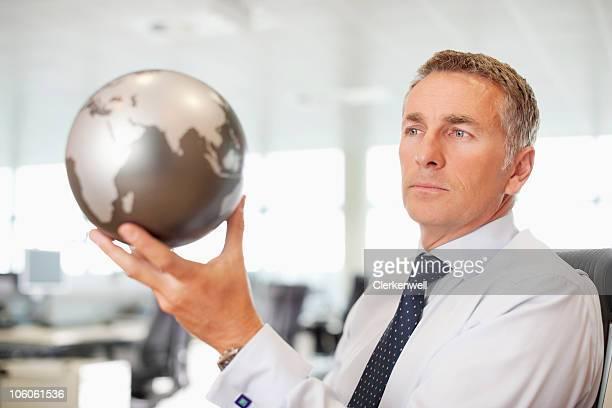 Graves maduro hombre de negocios mirando a un mundo