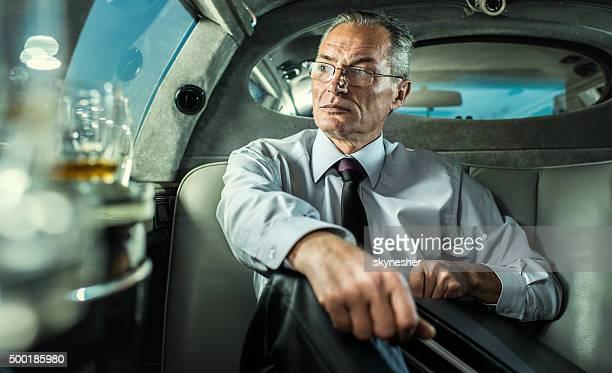 Ernst reifer Geschäftsmann Sie in einer limousine.