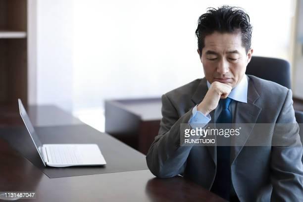 serious mature businessman with hand on chin at desk - 中年の男性一人 ストックフォトと画像