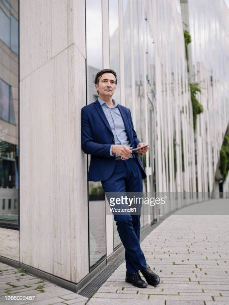 serious mature businessman with tablet leaning against a building in the city - leaning stock pictures, royalty-free photos & images
