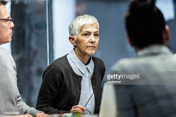 serious mature businesswoman attending a meeting in the office. - businesswear stock pictures, royalty-free photos & images